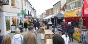 A photo of the Braintree Street Market along the High Street with stalls and people.