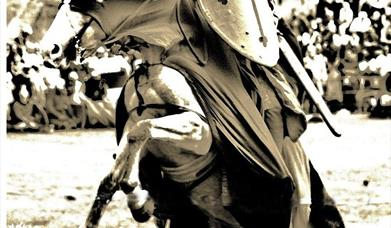 Sepia image of horse backed knight about to joust an opponent.