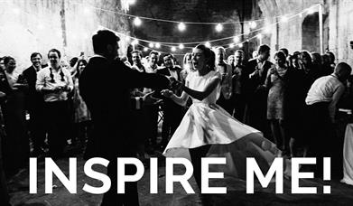 Black and white photo of a wedding party dancing with white text overlaid saying Inspire Me