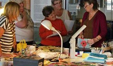 Five women talking over a creative work table